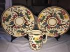 A pair of hand painted bowls and a small pouring pitcher.