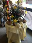Lovely yellow tablecloth with large silk flower arrangement, covered pie plates and other decorations