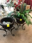 Pair of metal plant containers on stands one has silk flower arrangement in it