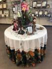 Round wooden table with tablecloth and decorative items which include flower arrangement candle holders and angel figurines