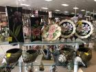 Two shelves with decorative items: large and medium size black vase with flowers, decorative plates and large sea shells as planters