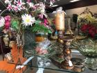 Two shelves of decorative items, flower arrangements, pedestal bowl's, candle holders and black containers with flowers on them