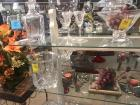 Two shelves of decorative glass items, decanter, candle holders, large leaded glass vase, ice bucket