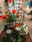 Grouping of decorative items: flower arrangement with orange flowers decorative lamp, green candles and bookends of magnolia flowers