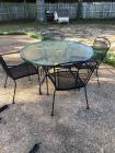Round glass top out door table with four metal chairs