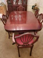 A beautiful clawfooted dining table with 6 chairs, 1 is a captain's chair