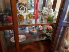 Two shelves of collectibles in curio cabinet.
