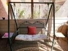 "Small metal porch swing. Dimensions including the frame are 53 x 38 x 61"" tall."
