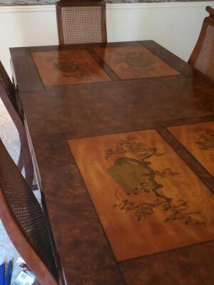 A spectacular dining table etched with Asian scenes and 8 chairs