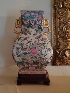 A gorgeous Asian vase on a wooden stand, vase has 2 gold colored handles