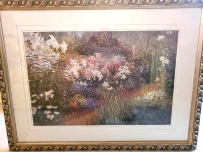A large framed and matted print of flowers in a garden
