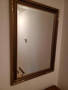 "Gold-colored framed mirror, 40"" tall x 29"" across"