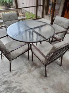 A glass topped patio table and 4 chairs with cushions, and an umbrella