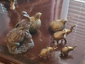 A grouping of 6 animals, 3 brass like elephants, 2 birds, and 2 matching statues of elephant s