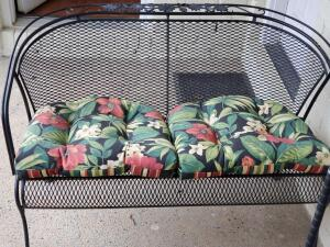 A wrought iron patio loveseat with cushions
