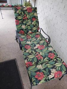 An iron patio adjustable lounger with cushions
