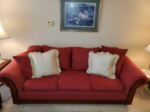 Wine color sofa with wood trim and 6 pillows.
