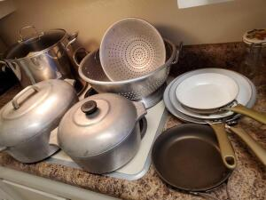 Grouping of cookware including calphalon skillet, WearEver ceramic coated skillets, vintage cast aluminum, stock pot, giant strainer and regular strai