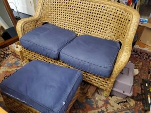 A wicker type loveseat with matching accent table