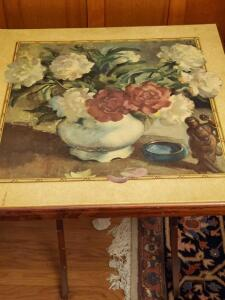 A vintage tilt top table with a beautiful picture on top