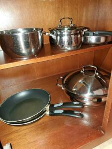 Cabinet of pans and skillets. Tools of the trade, mirro, two mixing bowls