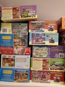 A shelf of artist series puzzles including Charles wysocki and board games.