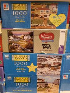 A shelf of artist series puzzles including Charles wysocki, Linda Nelson stocks, Jane Wooster Scott and more.