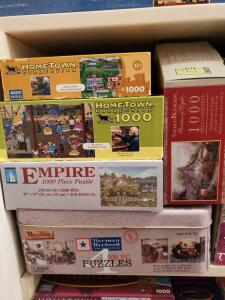 A shelf of artist series puzzles including Charles wysocki, Ann stookey, Norman Rockwell.