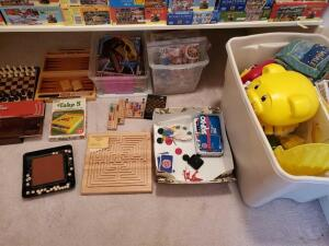 A container of kids puzzles, a container of kids toys and books, a magnetic chess game, backgammon board and other games.