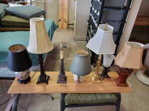 A grouping of seven lamps. 6 have shades.