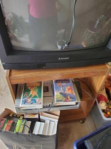 An entertainment cabinet with tv, vhs player and tape rewinder, a bag of vhs's