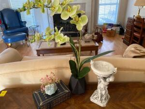 Grouping of decorative items on table: three books orchid silk plant, figurine