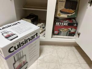 Items in cabinet: toaster, reverie stainless steel copper bottom pot, Cuisinart food processor, waffle maker, and other items in cabinet