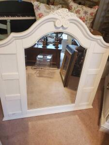 A large white mirror can can hold 6 pictures