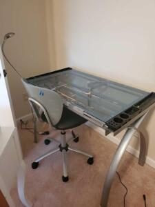 A glass topped drafting table with a light, and a chair