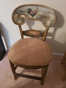 A padded barstool with a rooster and plants painted on it