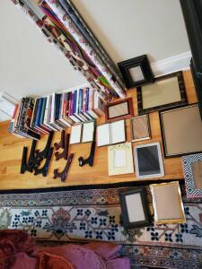 Miscellaneous grouping of books, wrapping paper, picture frames, and easels.