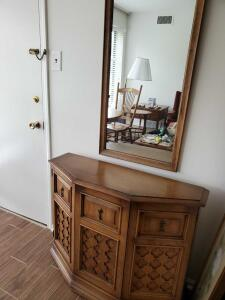 A decorative wooden cabinet with a matching mirror