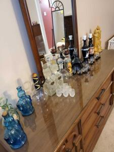 A large grouping of 13 decanters and several glasses. Also a portable bar.