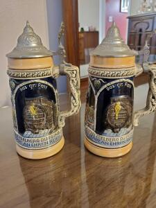 "A pair of matching German steins. 8"" tall"