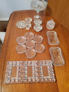 Assorted glassware accessories. Coasters, pedestal dish with flower frog, covered dish, candle holders, etc.