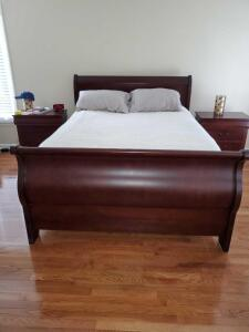 Cherry finish Queen-size sleigh bed with frame and rails. Bedding not included.