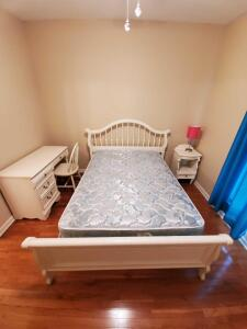 White full size bed, desk, chair, lamp and nightstand.