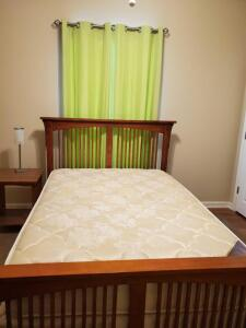 Full size bed and bedding, brown area rug.