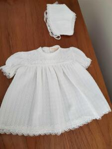 Lace trimmed christening dress with matching bonnet.