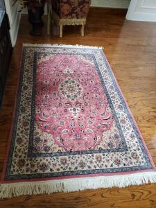 Lovely oriental style rug in foyer. Main color is rose.