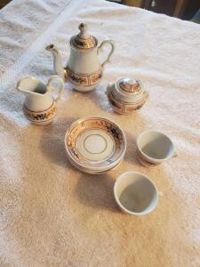 "An antique child's tea set (missing 2 cups), teapot is 4"", saucers are 3"""