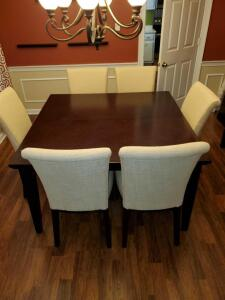 Expresso color Dining table and 6 light tan upholstered Parsons chairs.