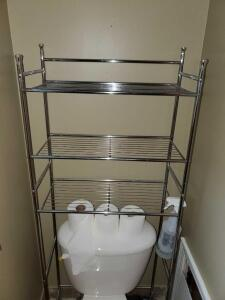 Metal shelf unit over the toilet and 3 bath rugs.