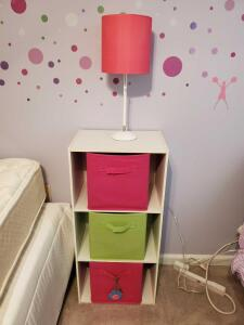 White storage shelf with green and pink baskets and a white lamp with a pink shade.